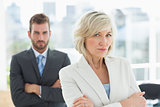 Mature businesswoman and young man with arms crossed