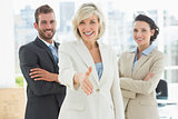Confident businesswoman offering handshake with team