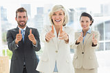 Confident business team gesturing thumbs up