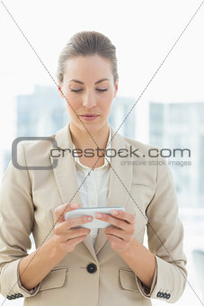 Beautiful young businesswoman text messaging