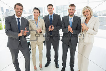 Business team clapping hands together in office