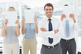 Businessman with colleagues holding blank paper in front of faces