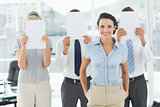 Businesswoman with colleagues holding blank paper in front of faces
