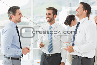 Business colleagues in discussion with tea cups during break