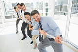 Group of business people pulling rope in office