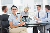 Businesswoman holding clipboard with colleagues discussing in office