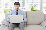 Well dressed man using laptop at home