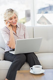 Businesswoman using mobile phone and laptop at home