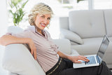 Beautiful businesswoman using laptop in living room