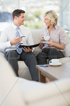 Businessman and his secretary  with diary and tea cup