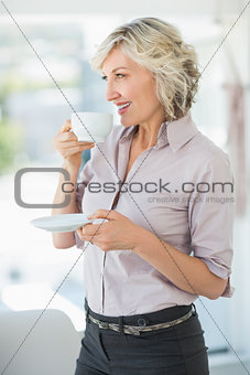 Smiling beautiful businesswoman drinking tea in office