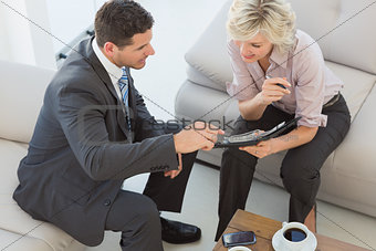 Businessman and his secretary  looking at diary at home