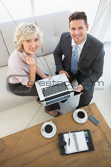 Businessman and his secretary with laptop and diary at home
