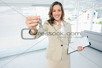Beautiful happy woman handing over house keys