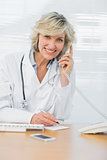 Female doctor using phone while writing notes