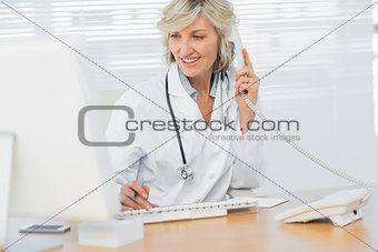 Doctor with computer using phone at medical office