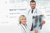 Female and male doctors with xray at medical office