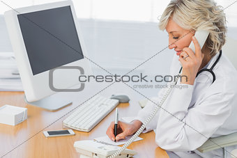 Female doctor using phone while writing notes at office