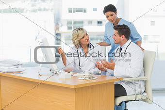 Three concentrated doctors using computer together