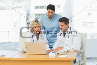 Three concentrated doctors using laptop together