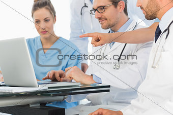 Group of concentrated doctors using laptop together