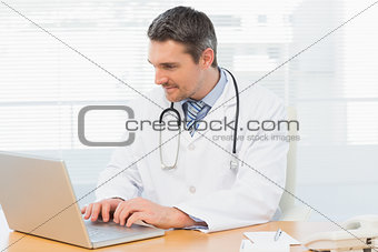 Doctor working on laptop at medical office