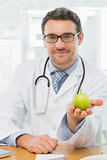 Portrait of a smiling male doctor holding an apple