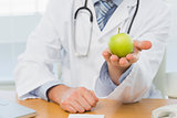 Mid section of a male doctor holding an apple