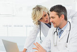 Two concentrated doctors using laptop together