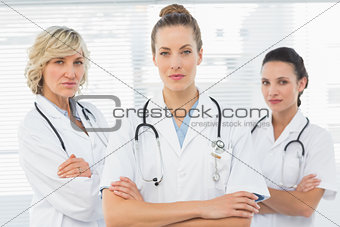 Three confident female doctors with arms crossed