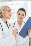 Two female doctors reading medical reports