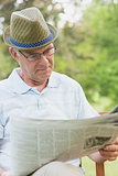 Senior man reading newspaper at park