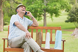 Cheerful relaxed senior man using mobile phone at park