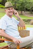 Relaxed senior man using mobile phone at park