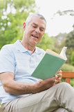 Senior man reading a book at park