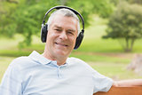 Smiling senior man with headphones at the park