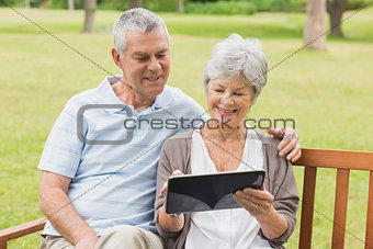 Senior couple using digital tablet on bench at park