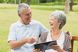 Cheerful senior couple using digital tablet on bench at park