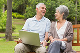 Cheerful senior couple using laptop at park