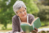 Senior woman reading a book at park