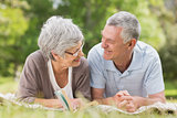 Smiling relaxed senior couple lying in park