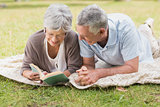 Relaxed senior couple reading book while lying in park