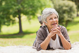 Smiling senior woman lying at park
