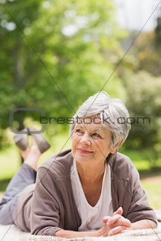Thoughtful senior woman lying at park