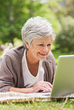 Smiling senior woman using laptop at park