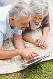 Smiling senior couple using digital tablet at park