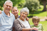 Smiling senior couple and grandchildren at park