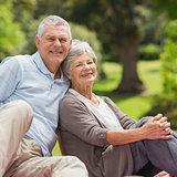 Smiling senior couple sitting at park