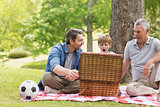 Grandfather, father and son with picnic basket