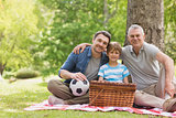 Grandfather, father and son with picnic basket at park
